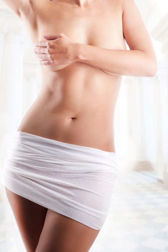 Close-up of a woman's toned midsection after liposuction of the flanks