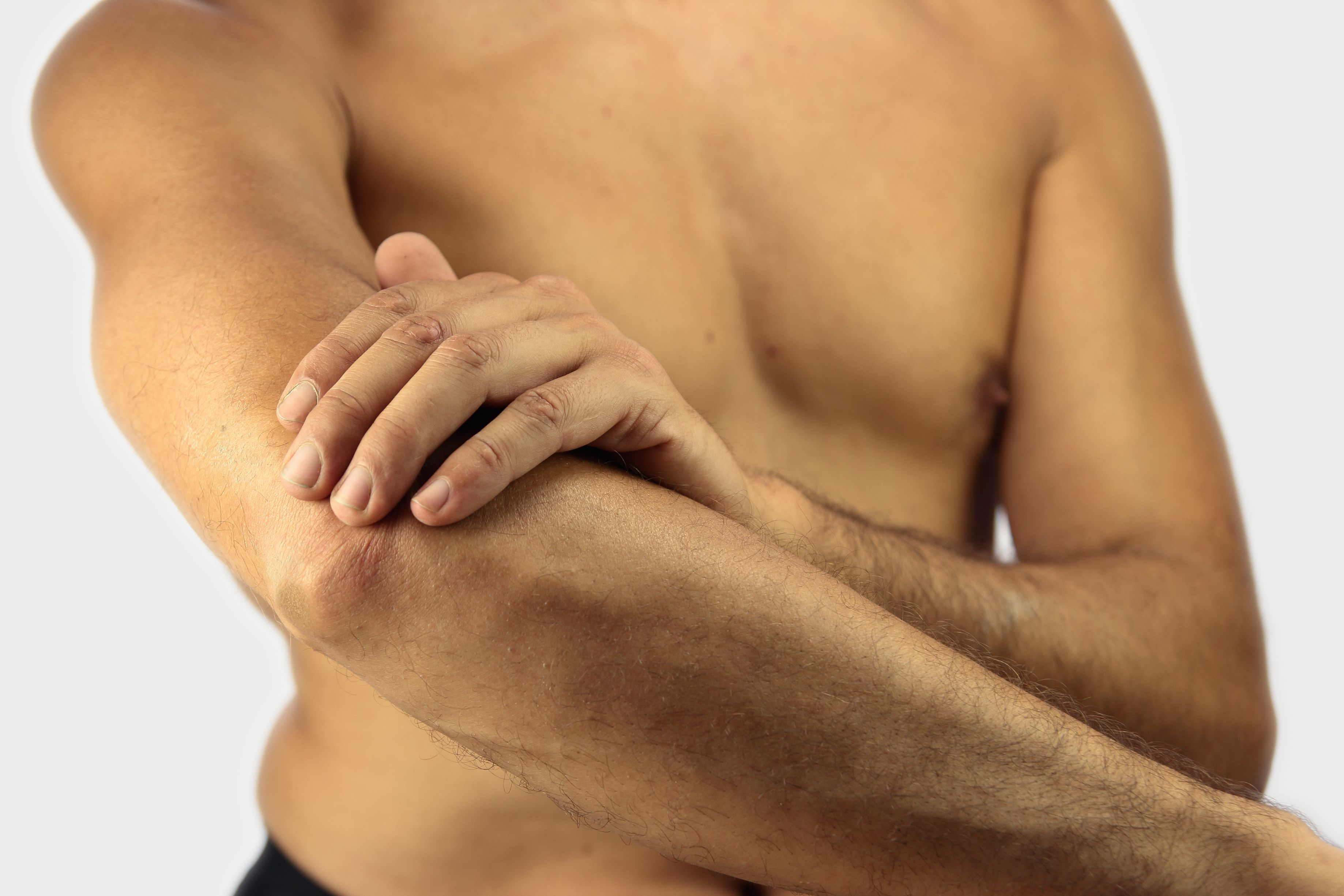 Photo of a man holding his elbow
