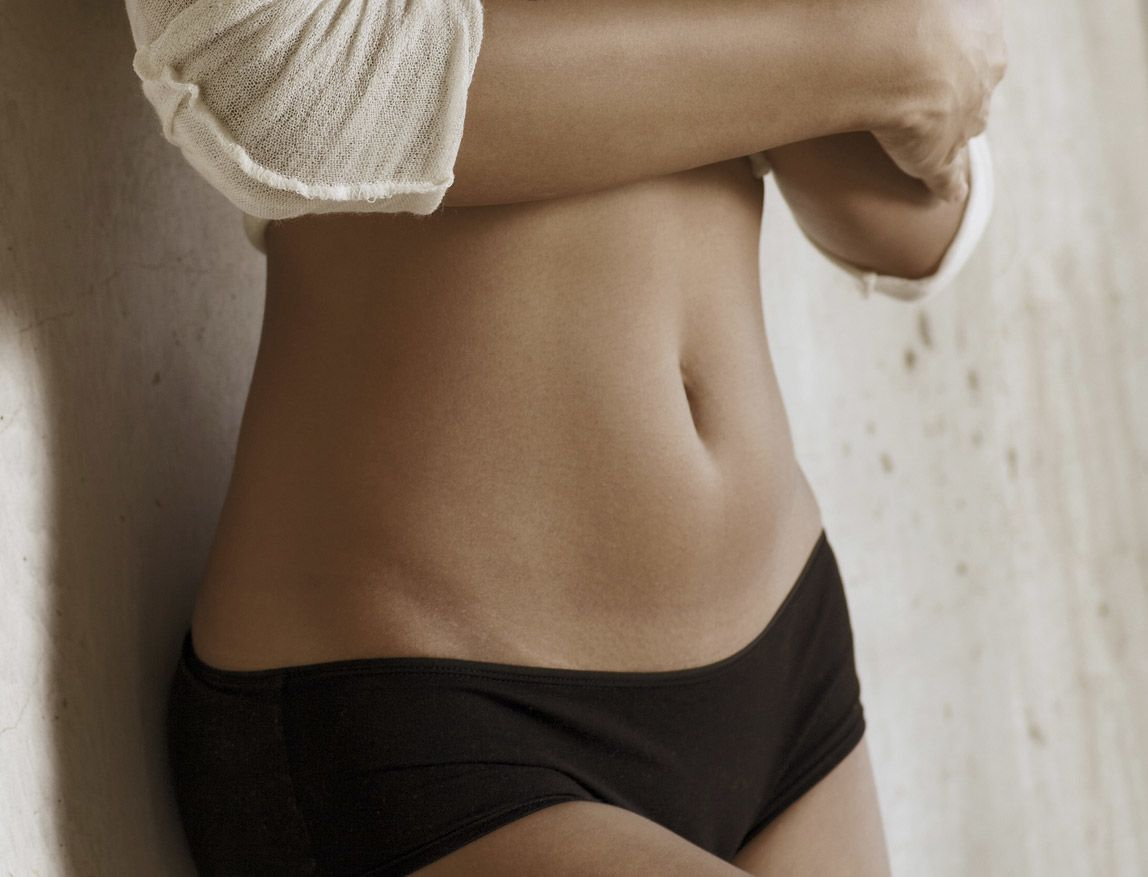 Close-up of a patient's tight, toned abdomen after tummy tuck surgery