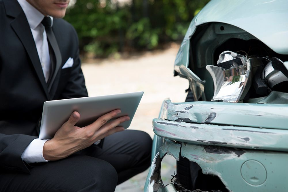 Man in a suit crouches in front of a damaged car headlight with a tablet.
