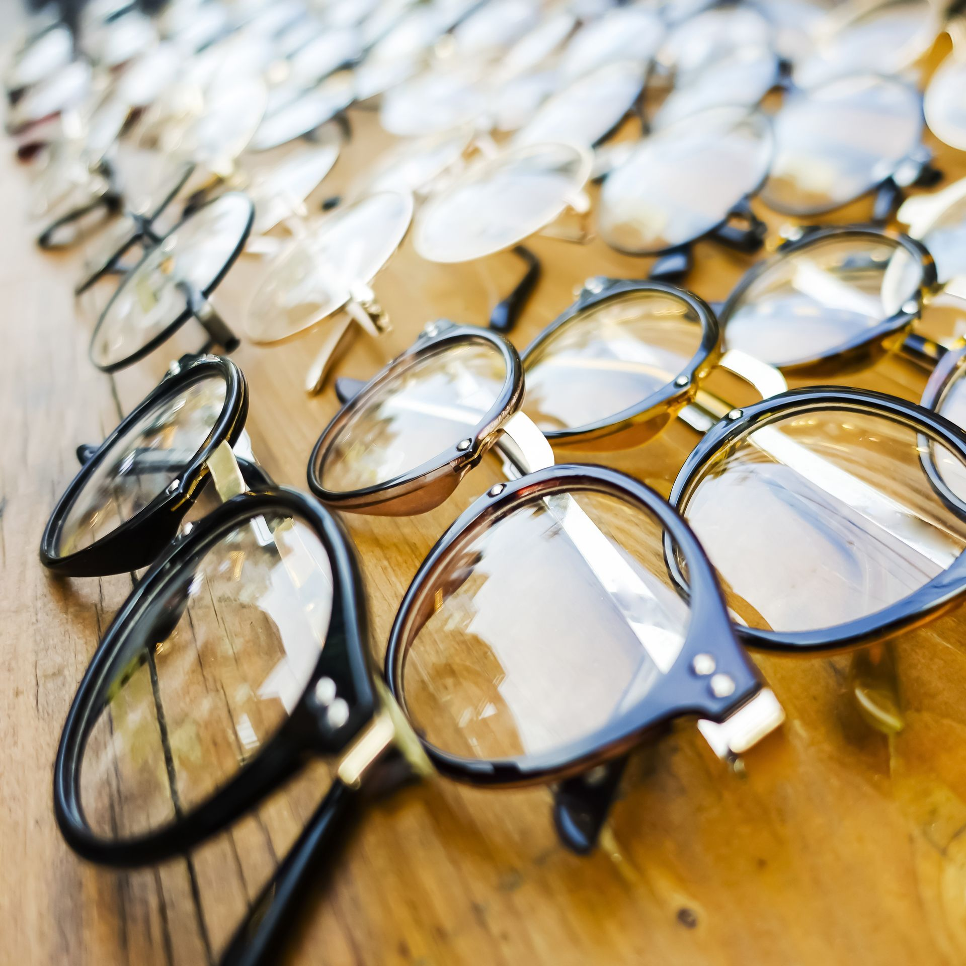 Photo of several eyeglasses frames displayed on a wooden surface