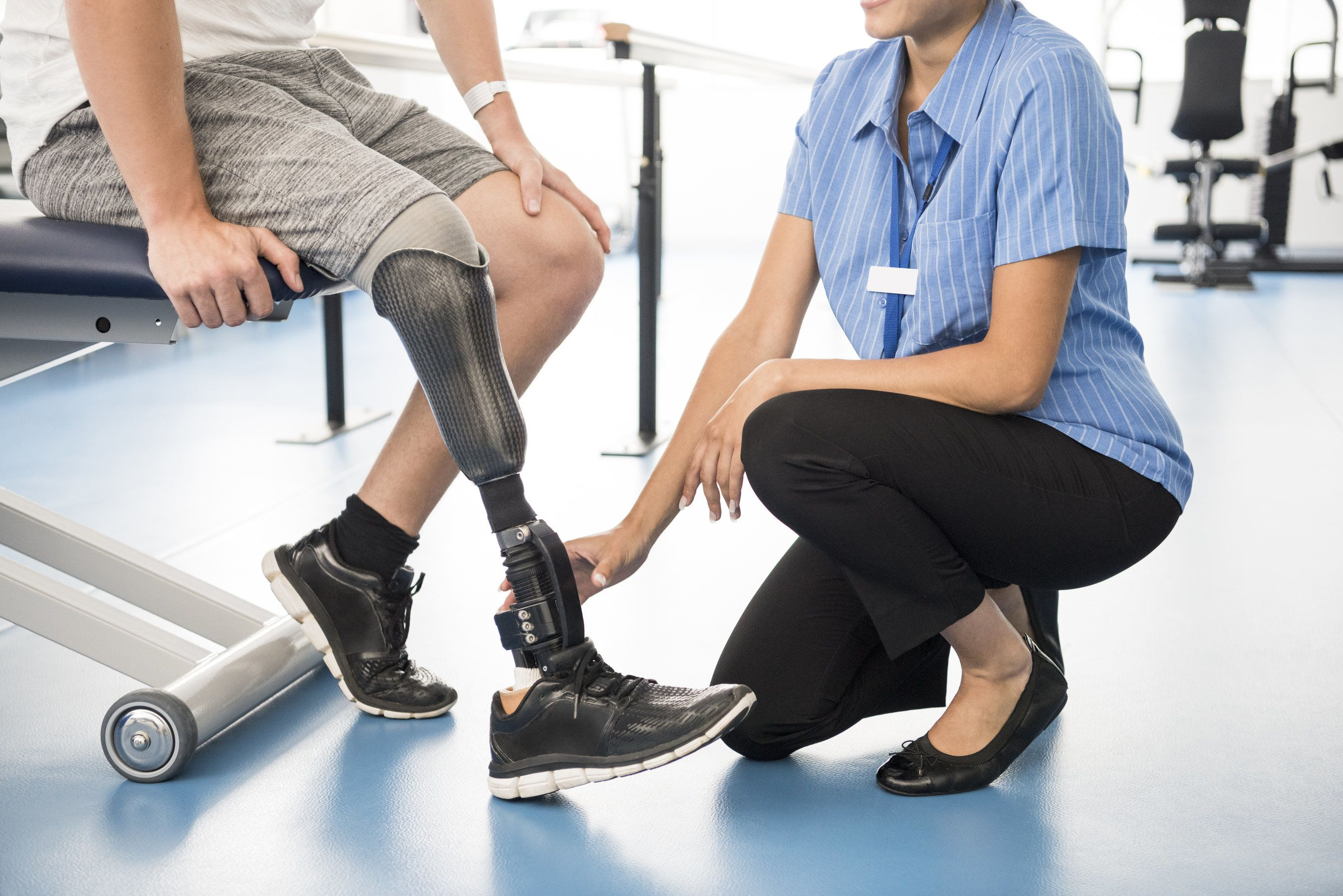 A physical therapist working with a patient with a prosthetic leg