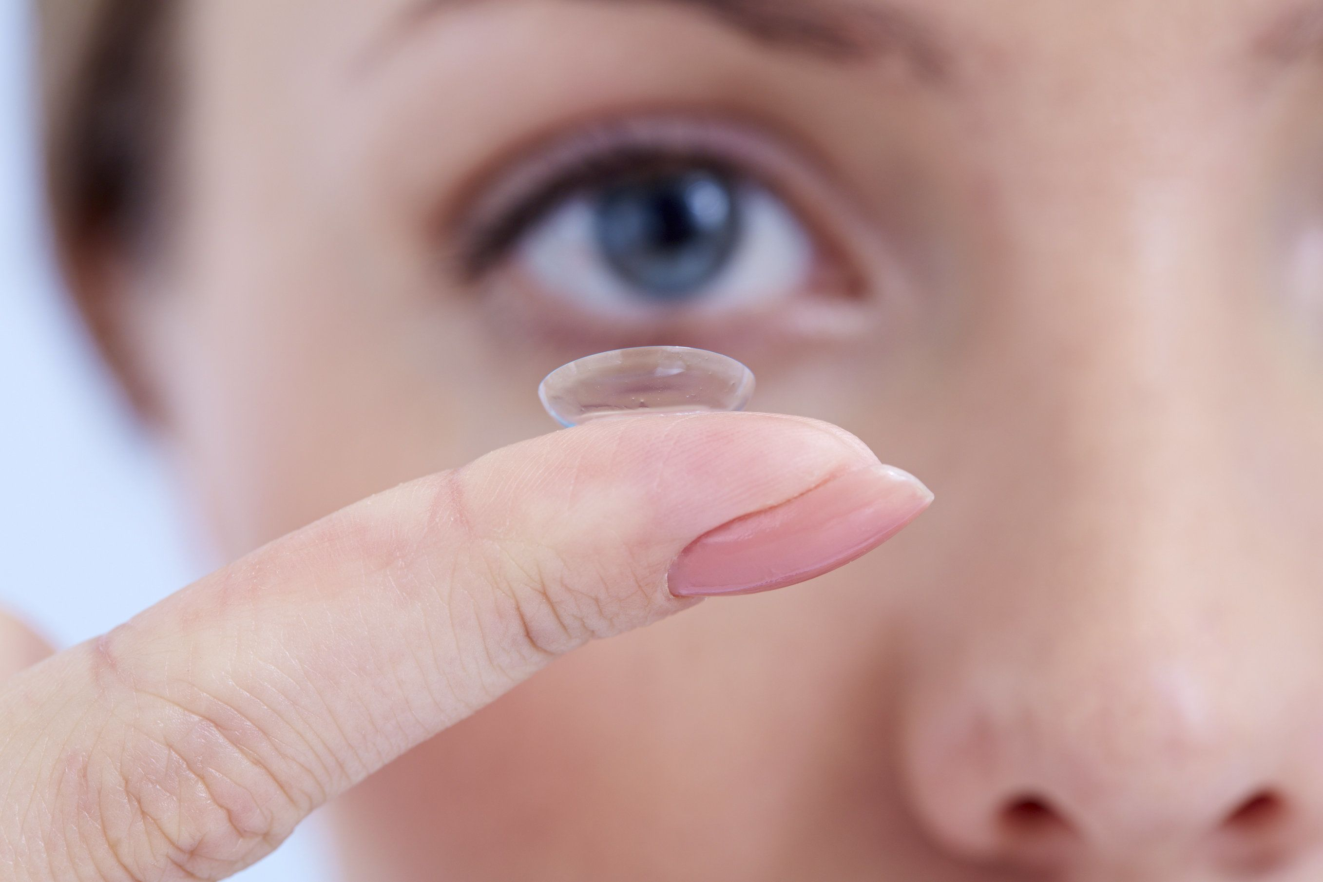 Single contact lens held in front of woman's right eye
