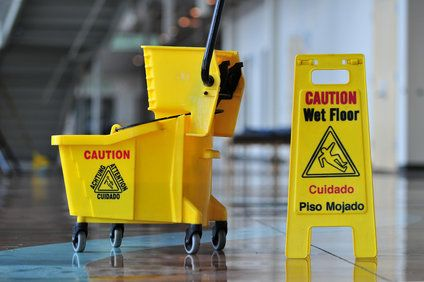 A wet floor sign and mop bucket
