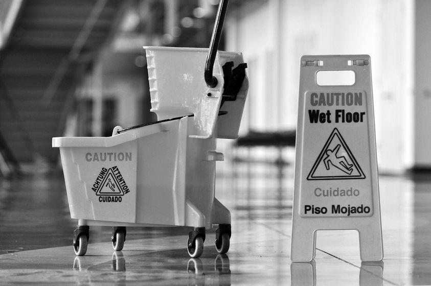A wet floor sign near a mop