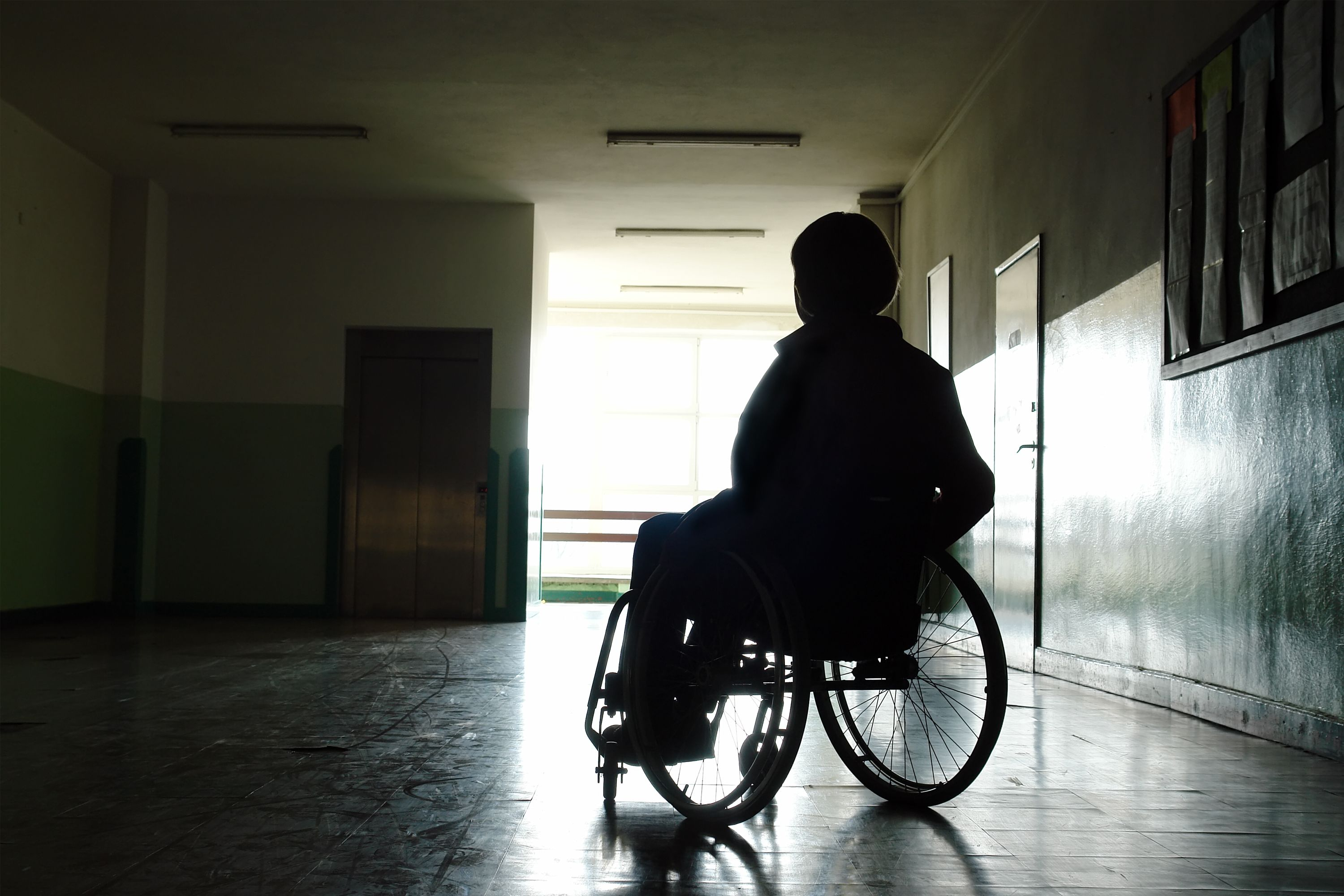 A person in a wheelchair in a dark hallway