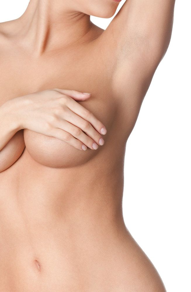 A woman holding her breast after undergoing breast augmentation using the inframammary incision technique
