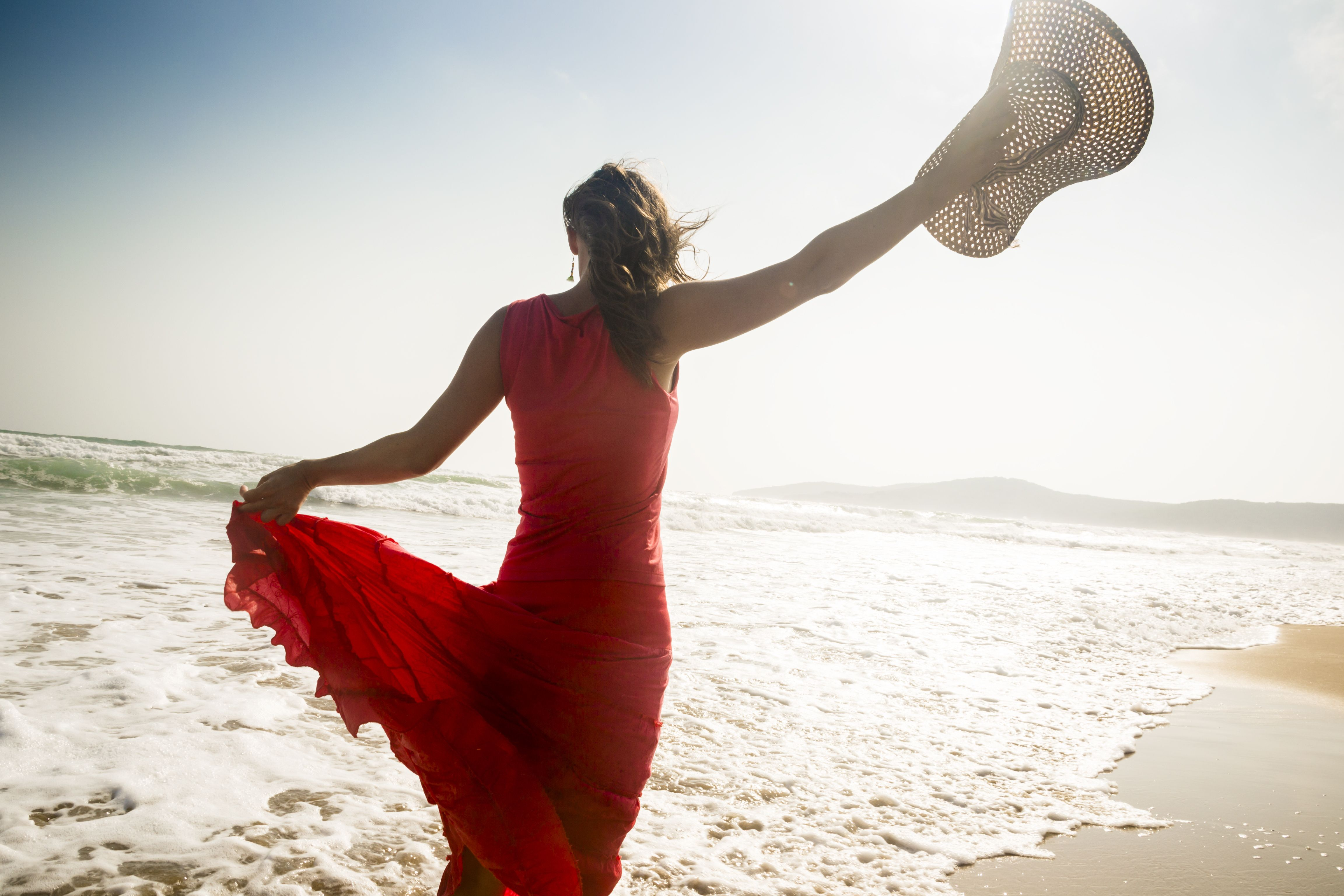 Woman in red dress walking away along sunlight beach