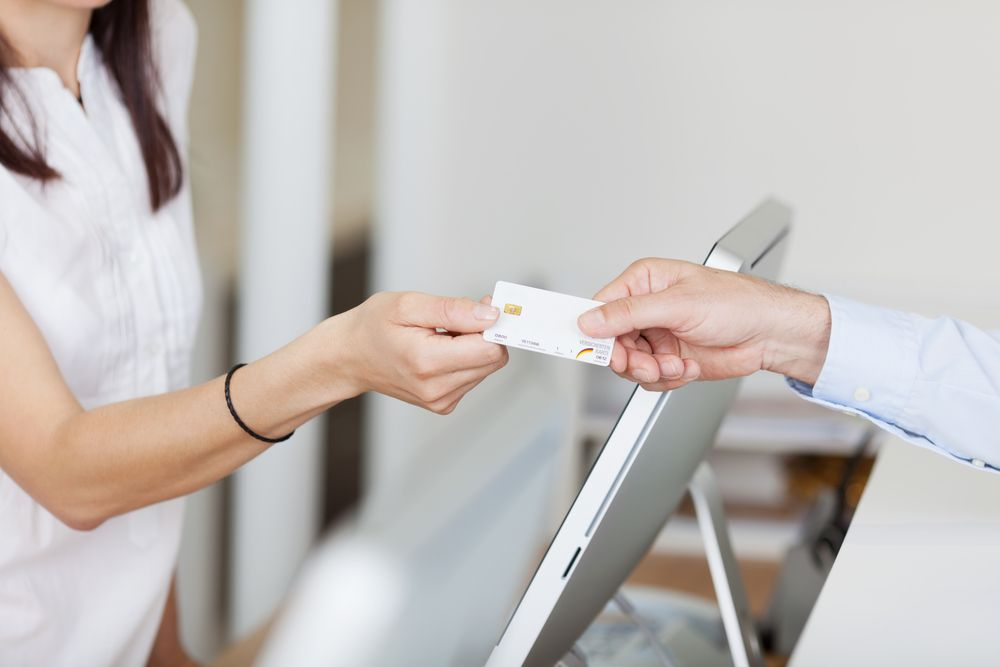 Woman handing receptionist credit card