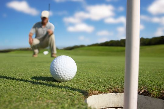 A man rolling a golf ball toward a hole on a green.