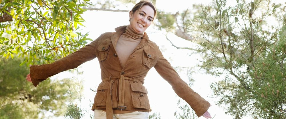 Smiling woman in forest spreading arms wide