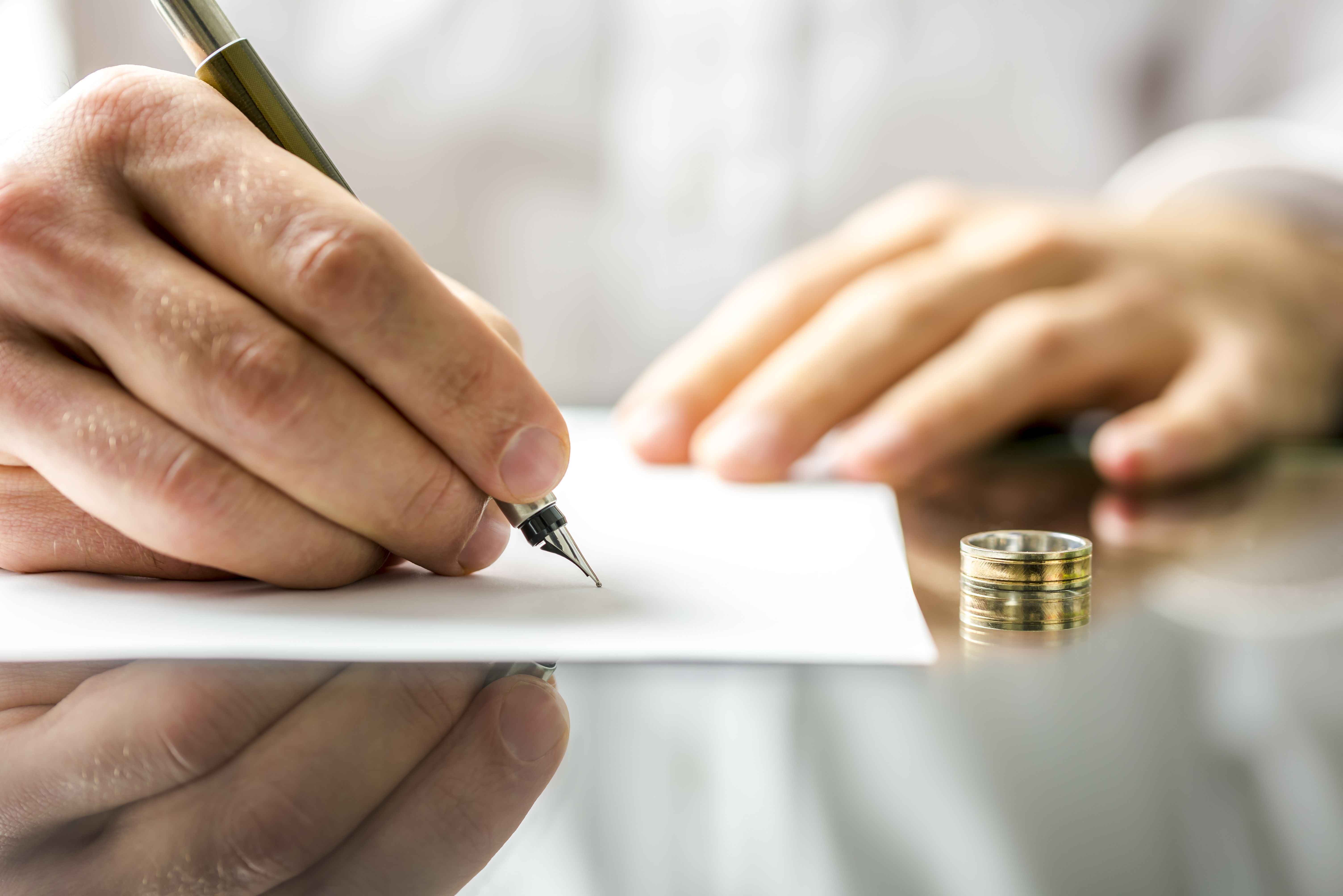 Man signing paperwork with wedding ring on the table