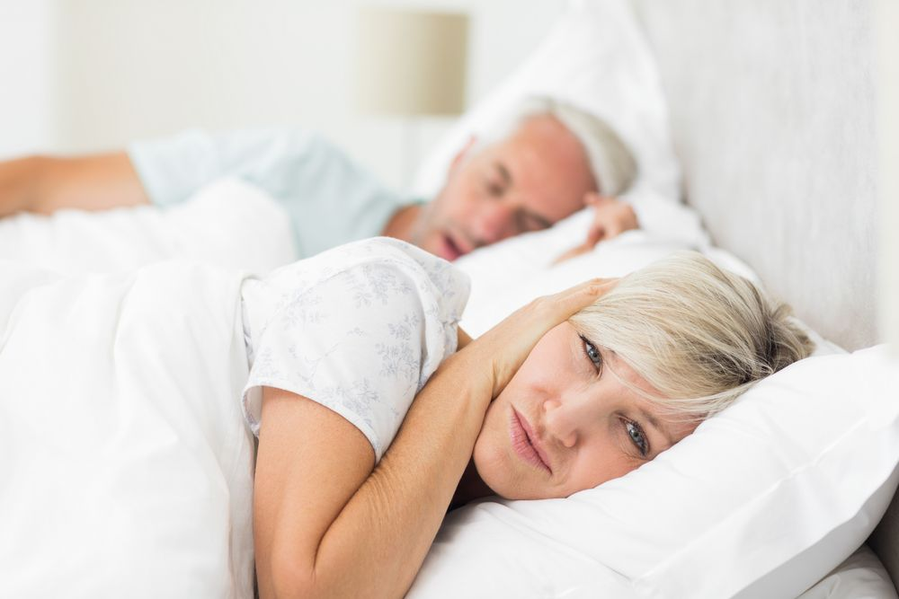 A man snoring and a woman covering her ears