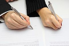 A man and woman signing divorce papers
