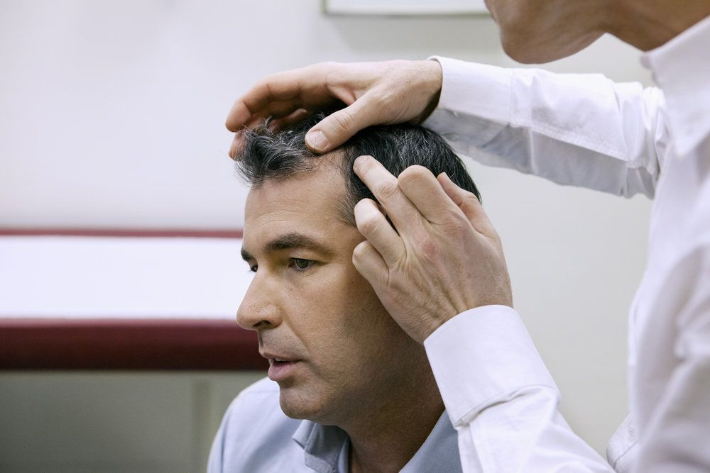 A hair surgeon inspecting a patient's hair ten months after hair transplant surgery