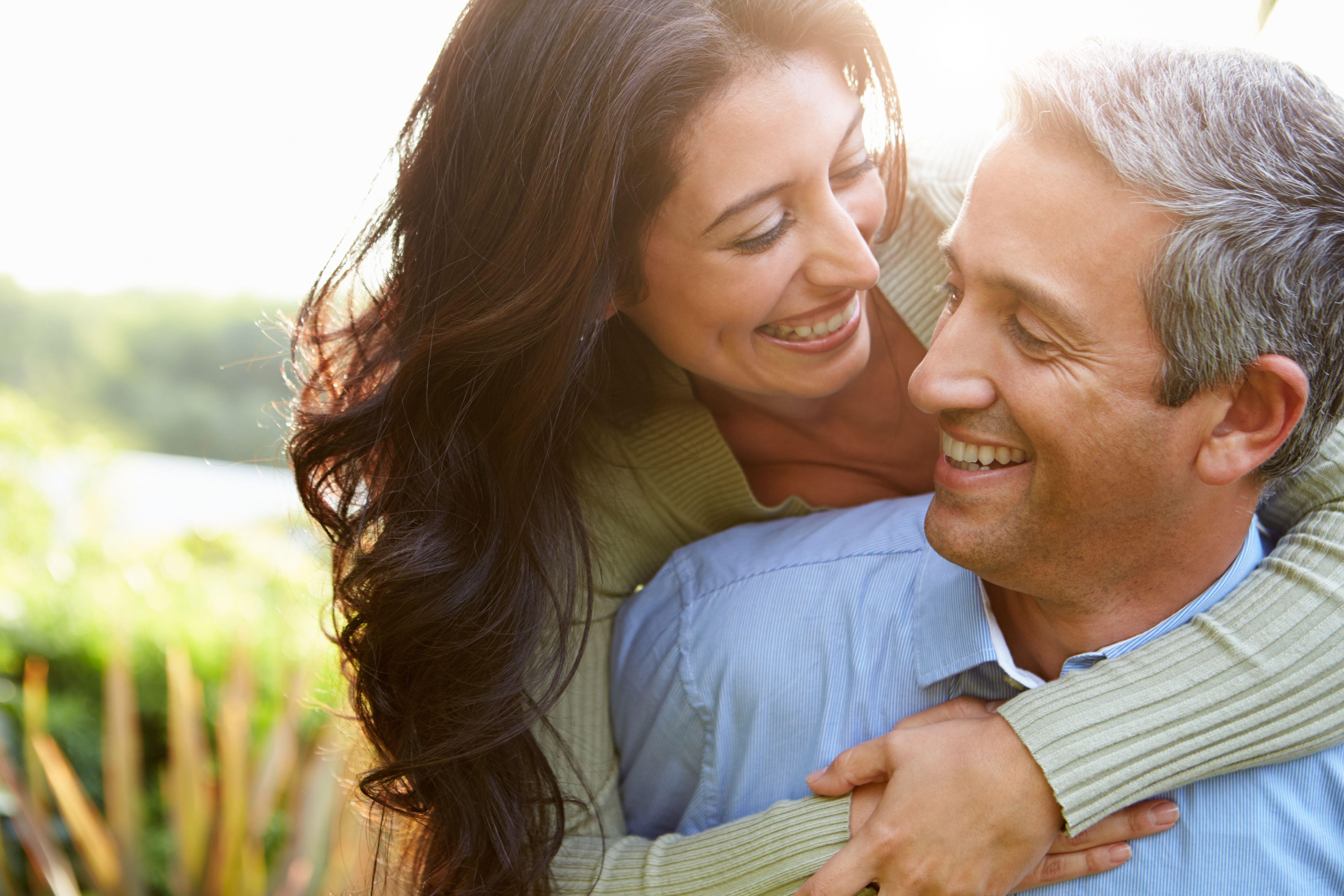 Woman hugging man, both smiling with healthy-looking teeth