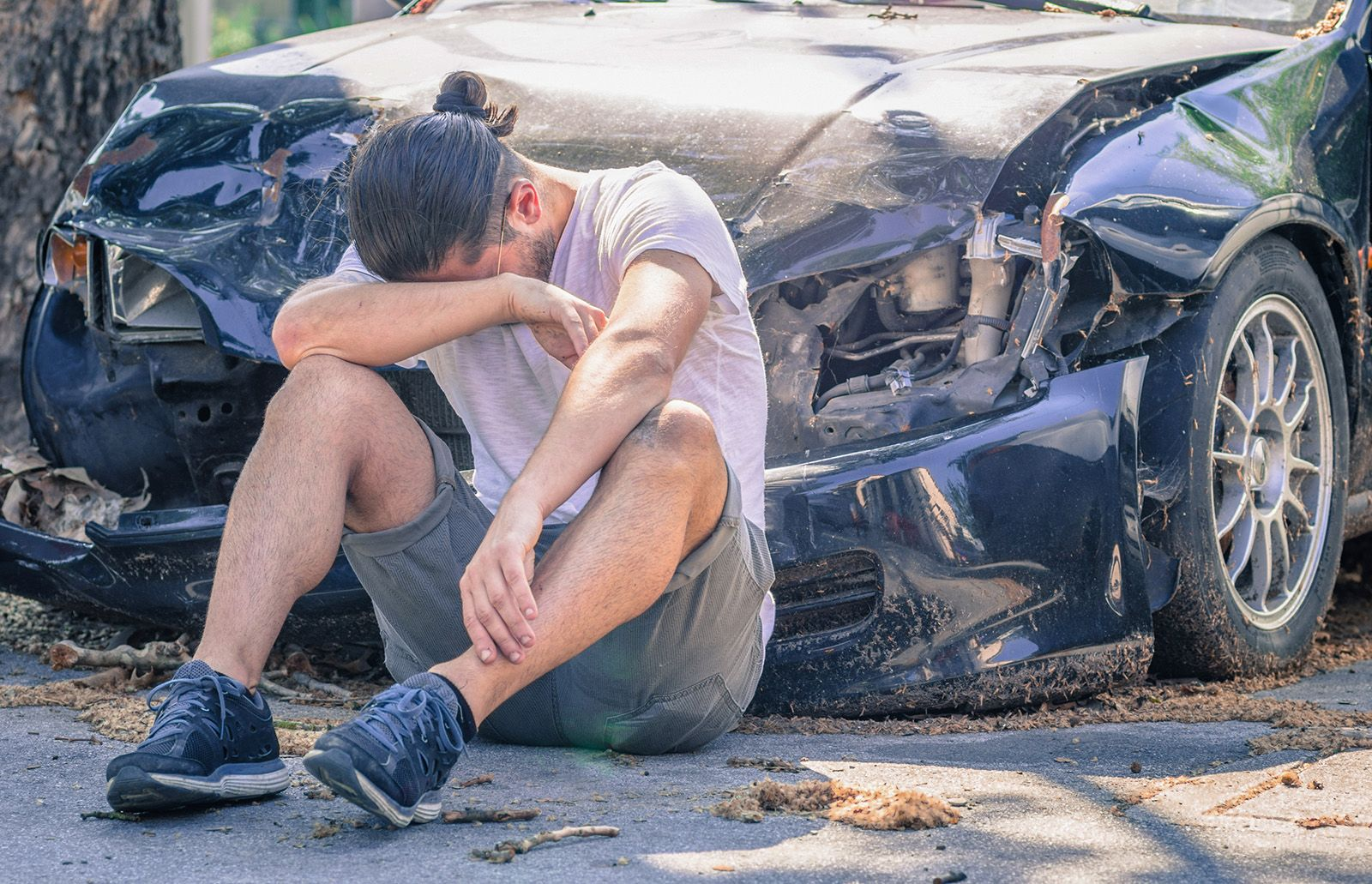 Upset man in front of wrecked car