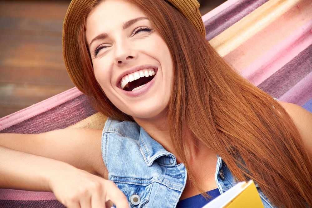 Laughing young woman in a hammock