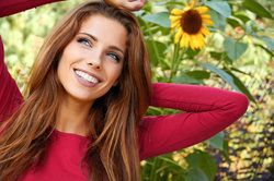 A woman smiling beside a sunflower