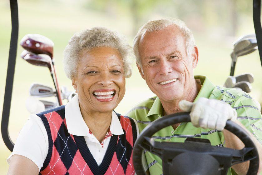 Senior biracial couple driving a golf cart