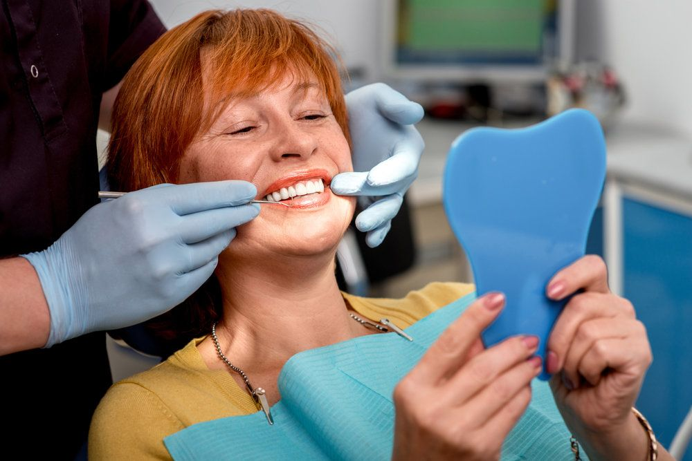 Middle-aged woman with red hair receiving dental exam