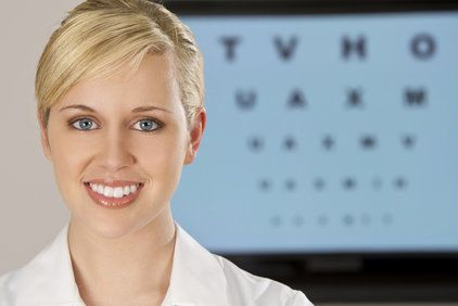 A beautiful blonde woman standing in front of an eye chart.