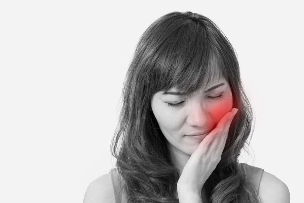 Black and white photo of woman with toothache