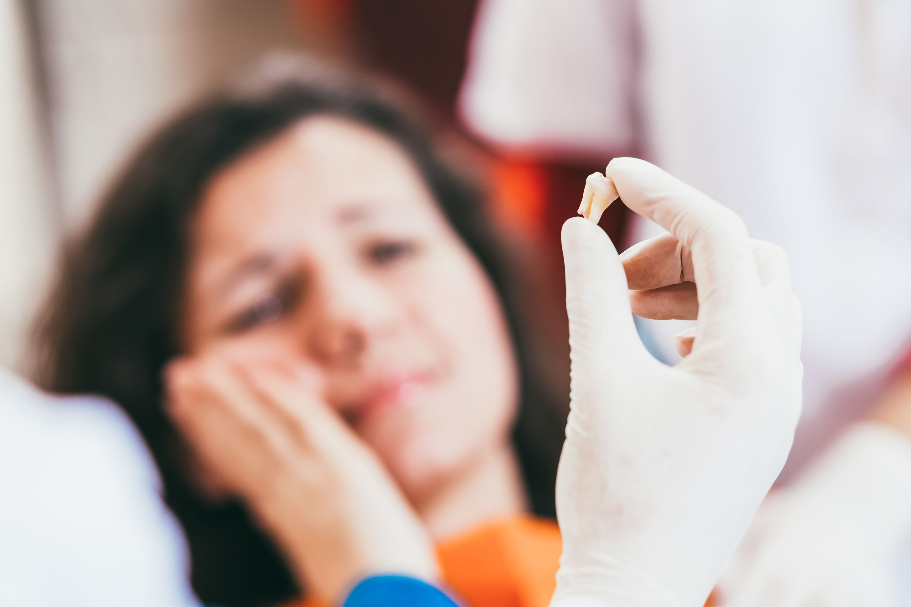 A woman with a toothache and a dentist holding up an extracted tooth