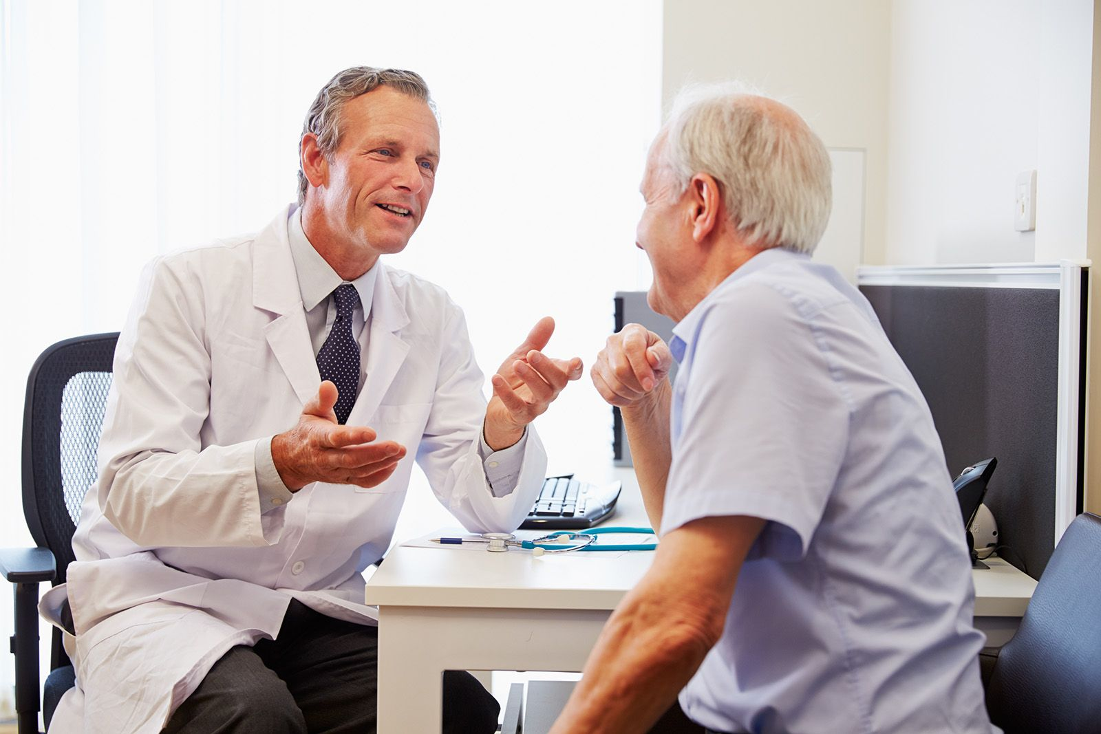 Male doctor conducting consultation with older male patient