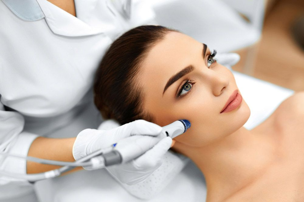 Attractive female patient reclines on bed while receiving skin laser treatment
