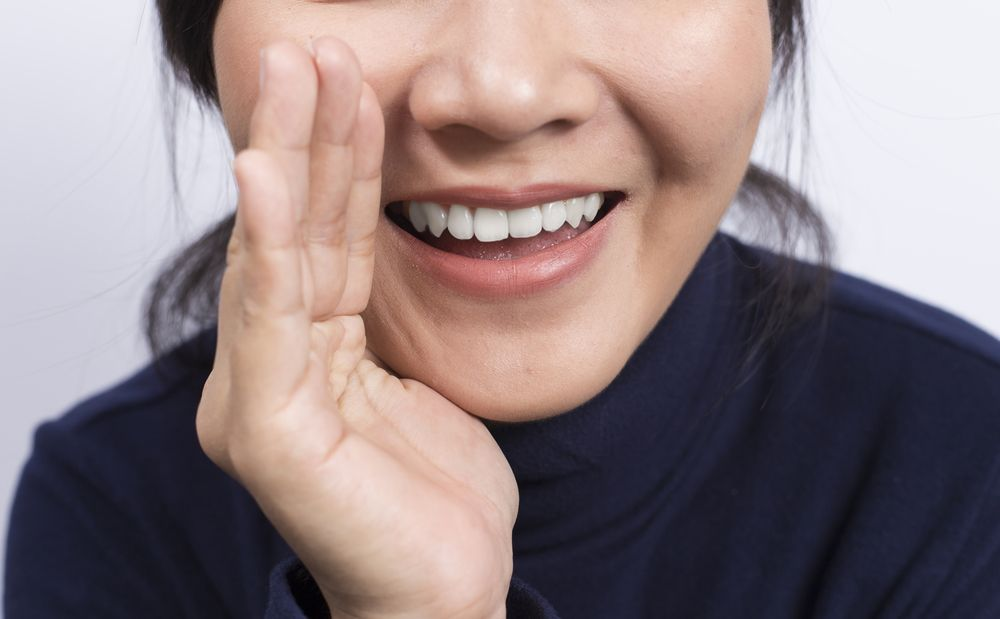Up close photo of woman whispering with hand up to her face