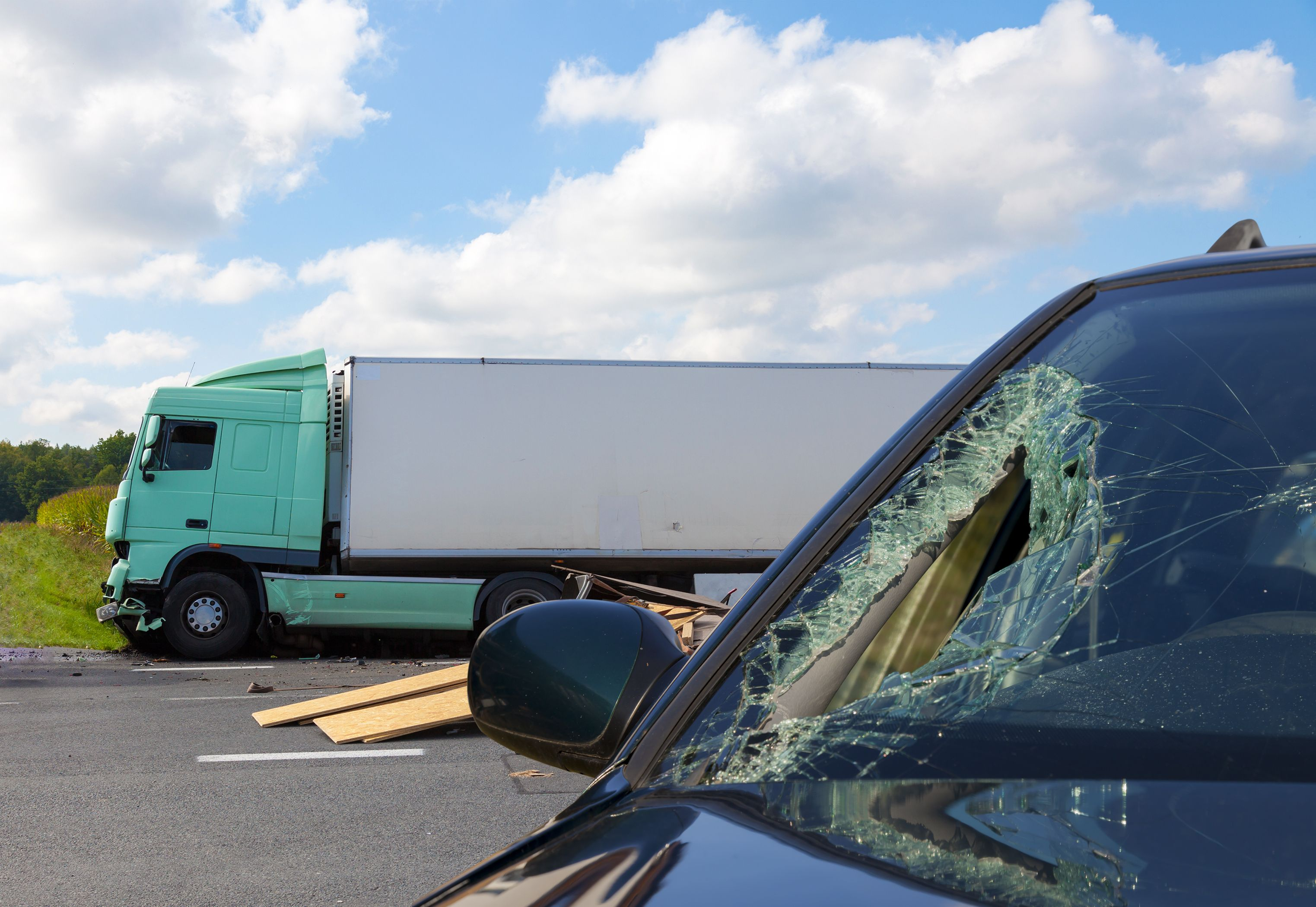 A broken windshield and a large commercial truck