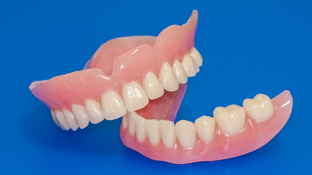 Photo of upper and lower dentures on solid blue surface