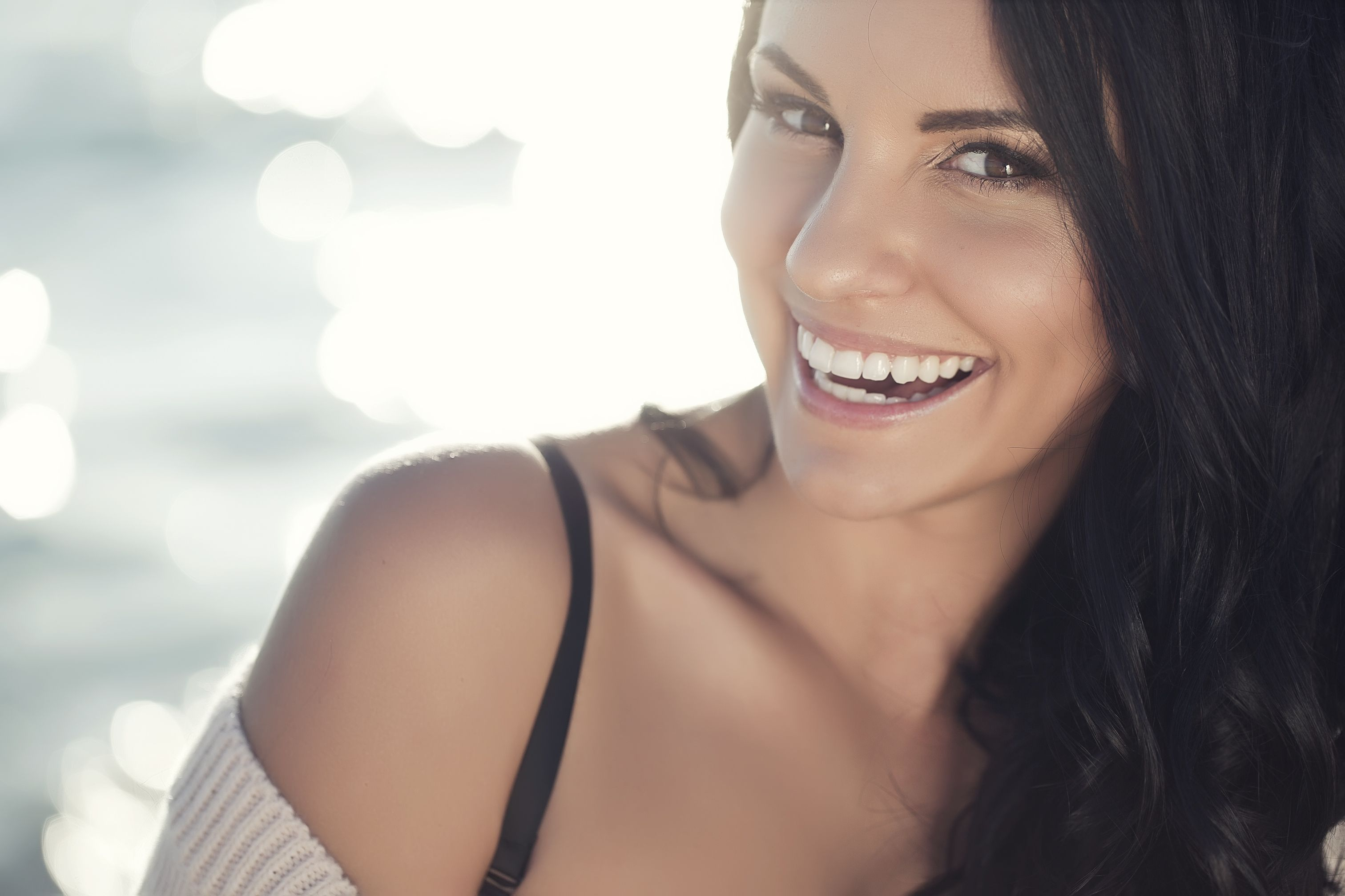 A woman smiling broadly because she has taken years off her appearance through facial plastic surgery