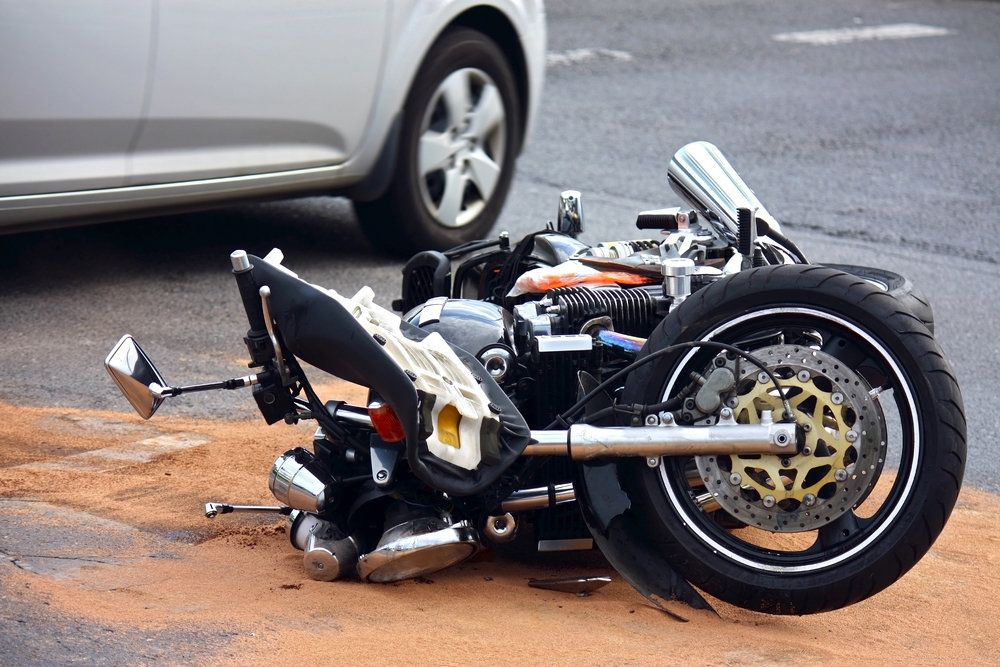 Motorcycle lying down on its side in the road