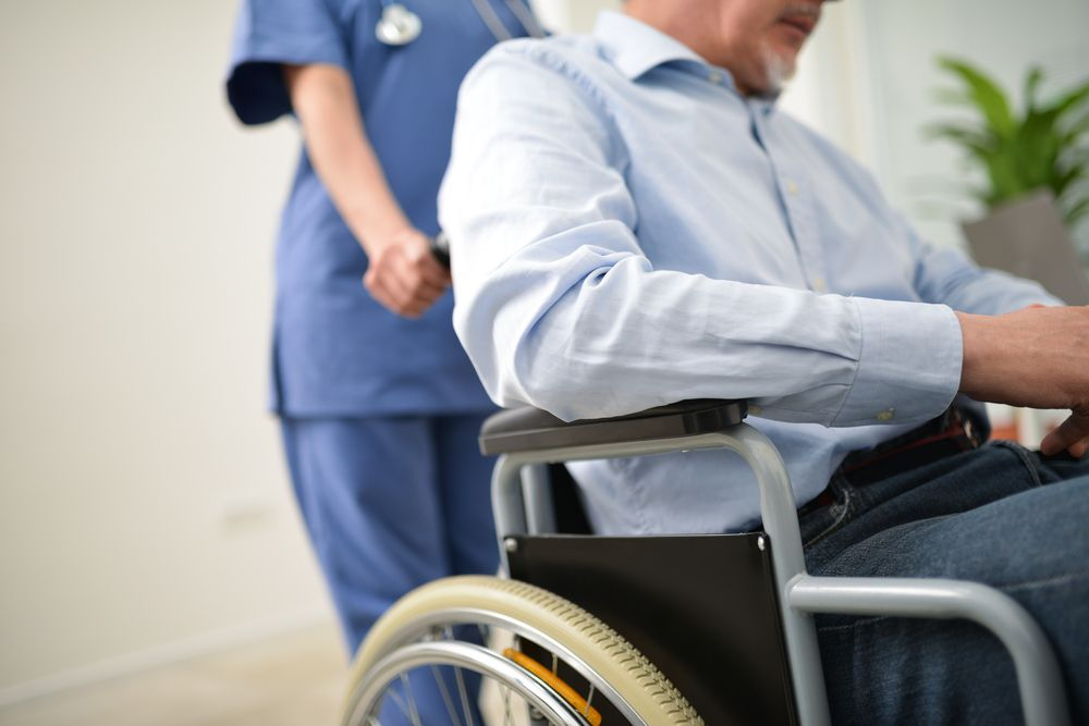 A man in a wheelchair pushed by a nurse