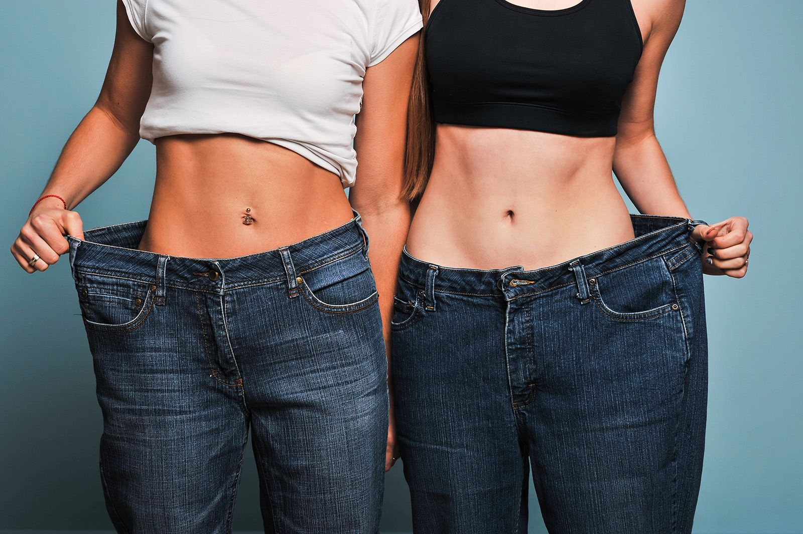 photo of two women standing in their old jeans after weight loss surgery