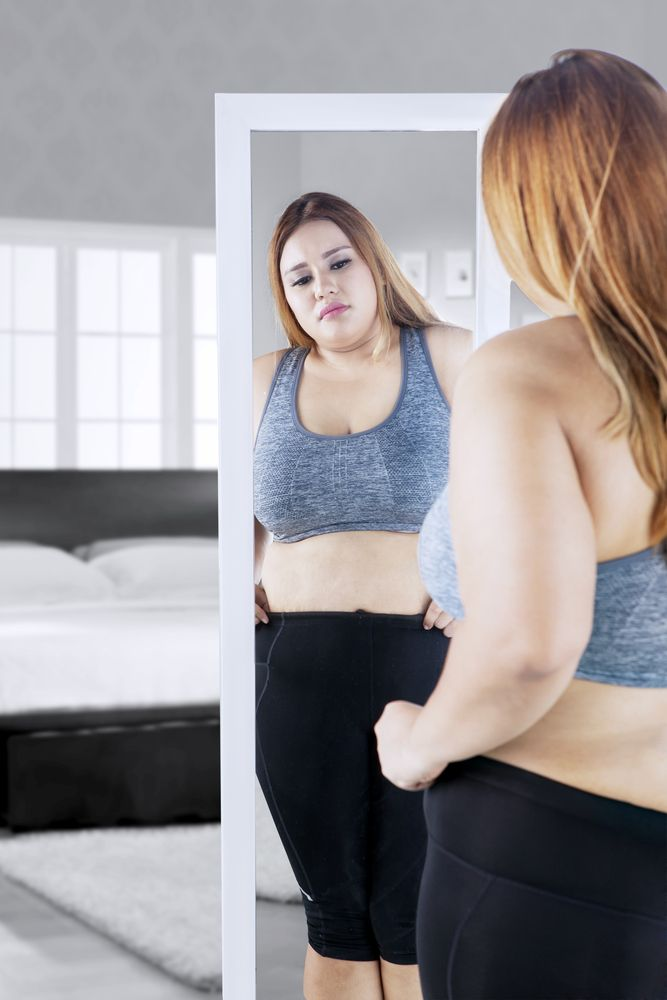 Woman looking in the mirror after weight gain