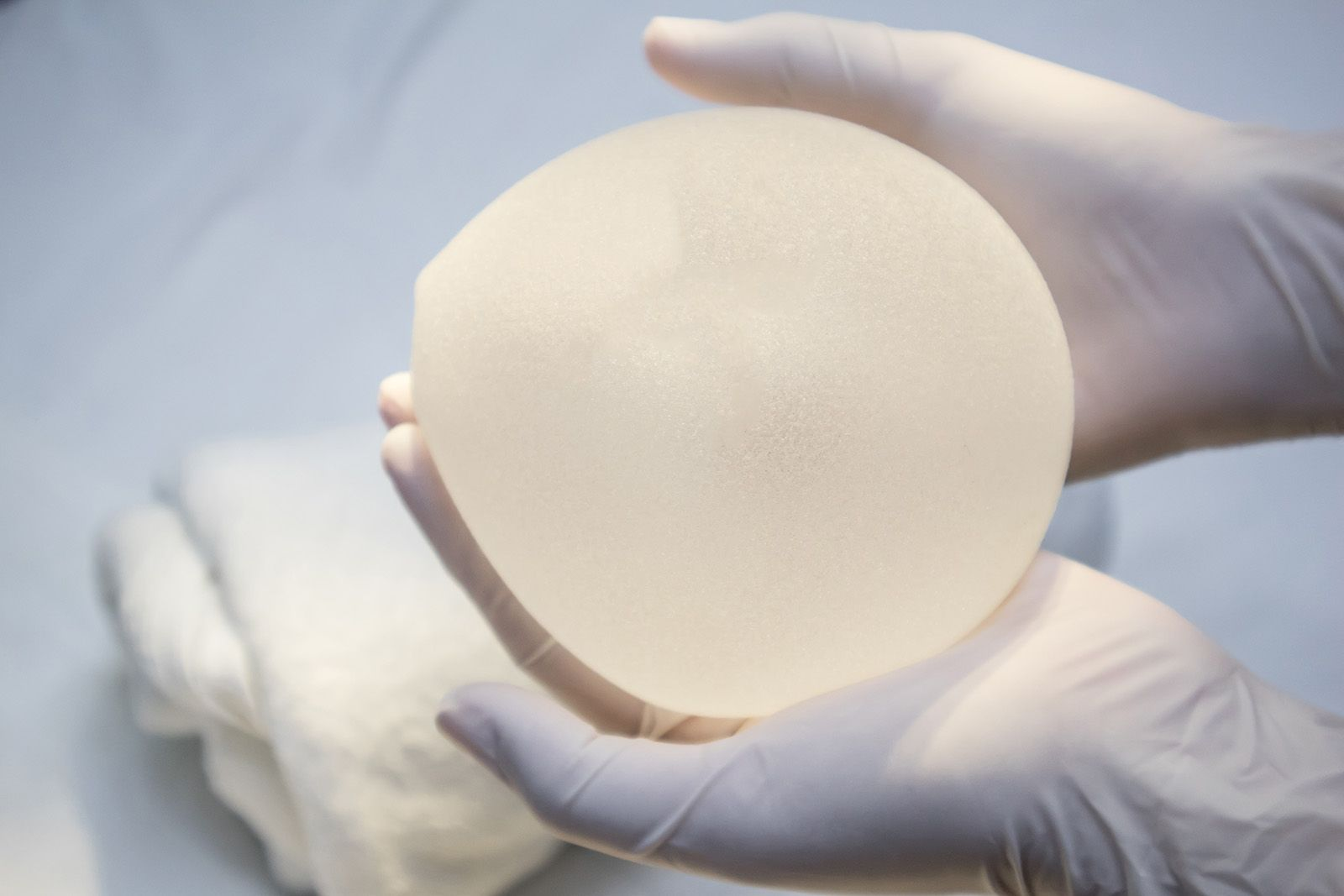 Up close photograph of a medical professional holding a breast implant