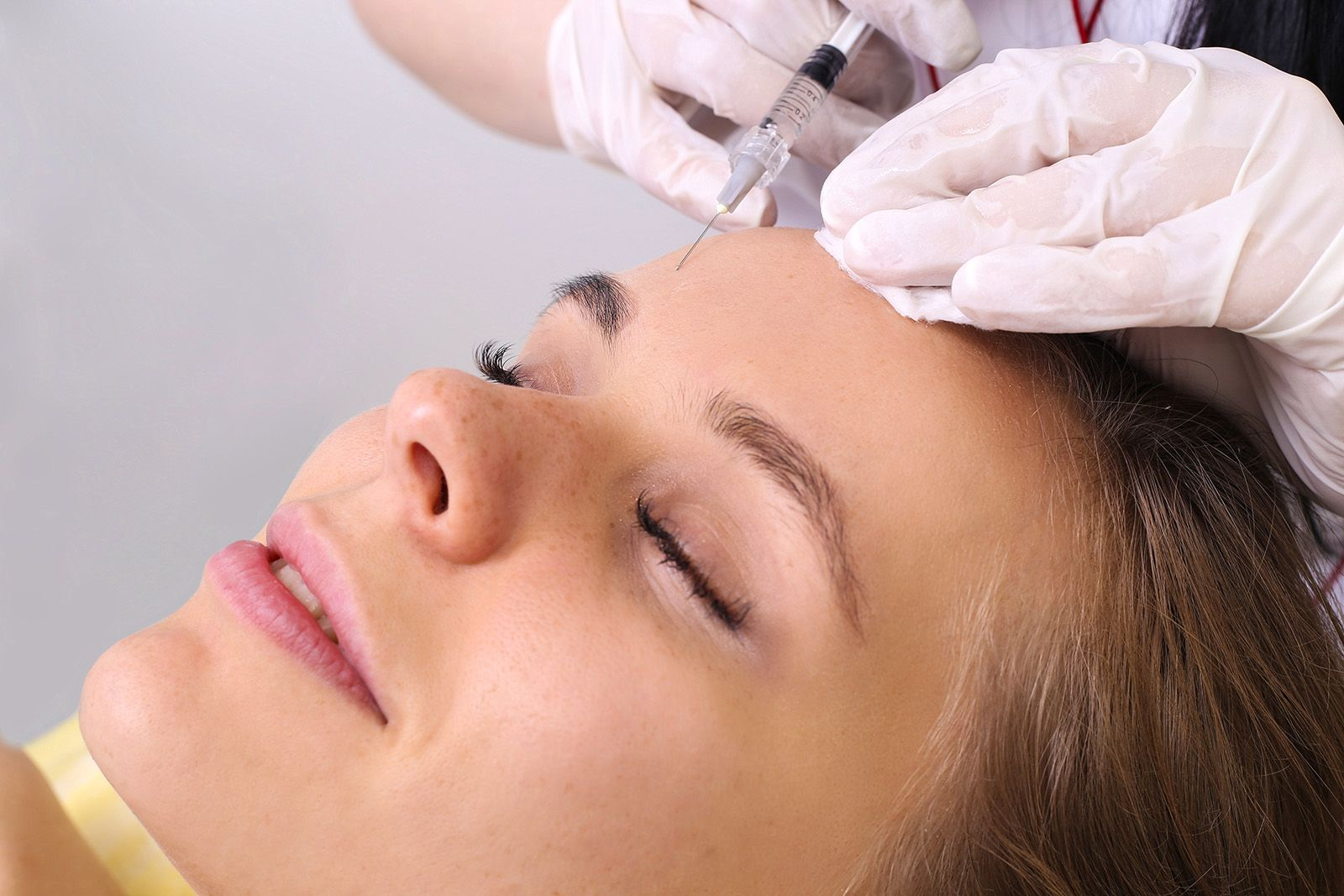 A woman undergoing BOTOX injection treatment