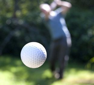 Action shot of a golf ball flying mid-air.