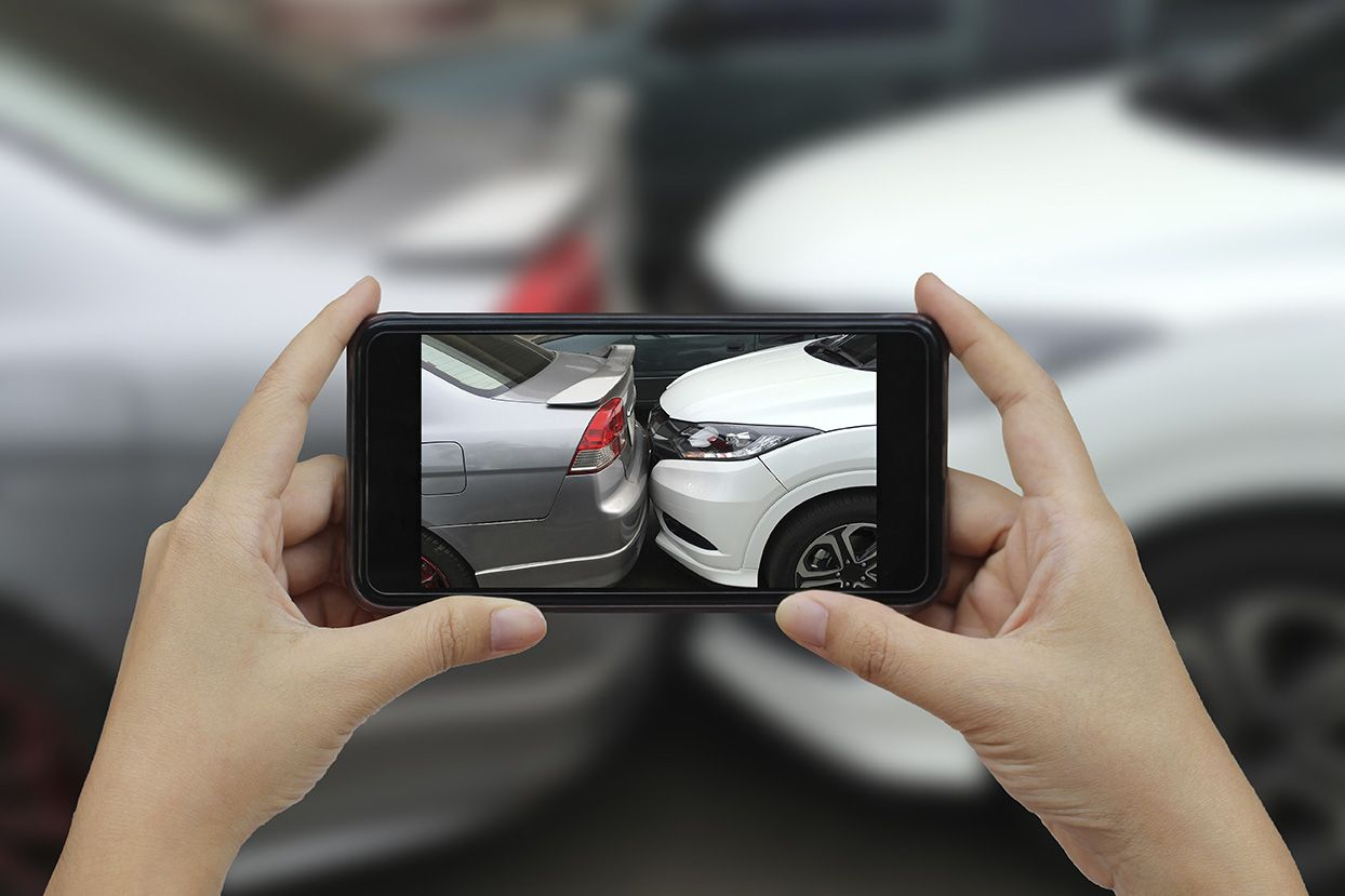 Woman taking picture of car accident on smart phone