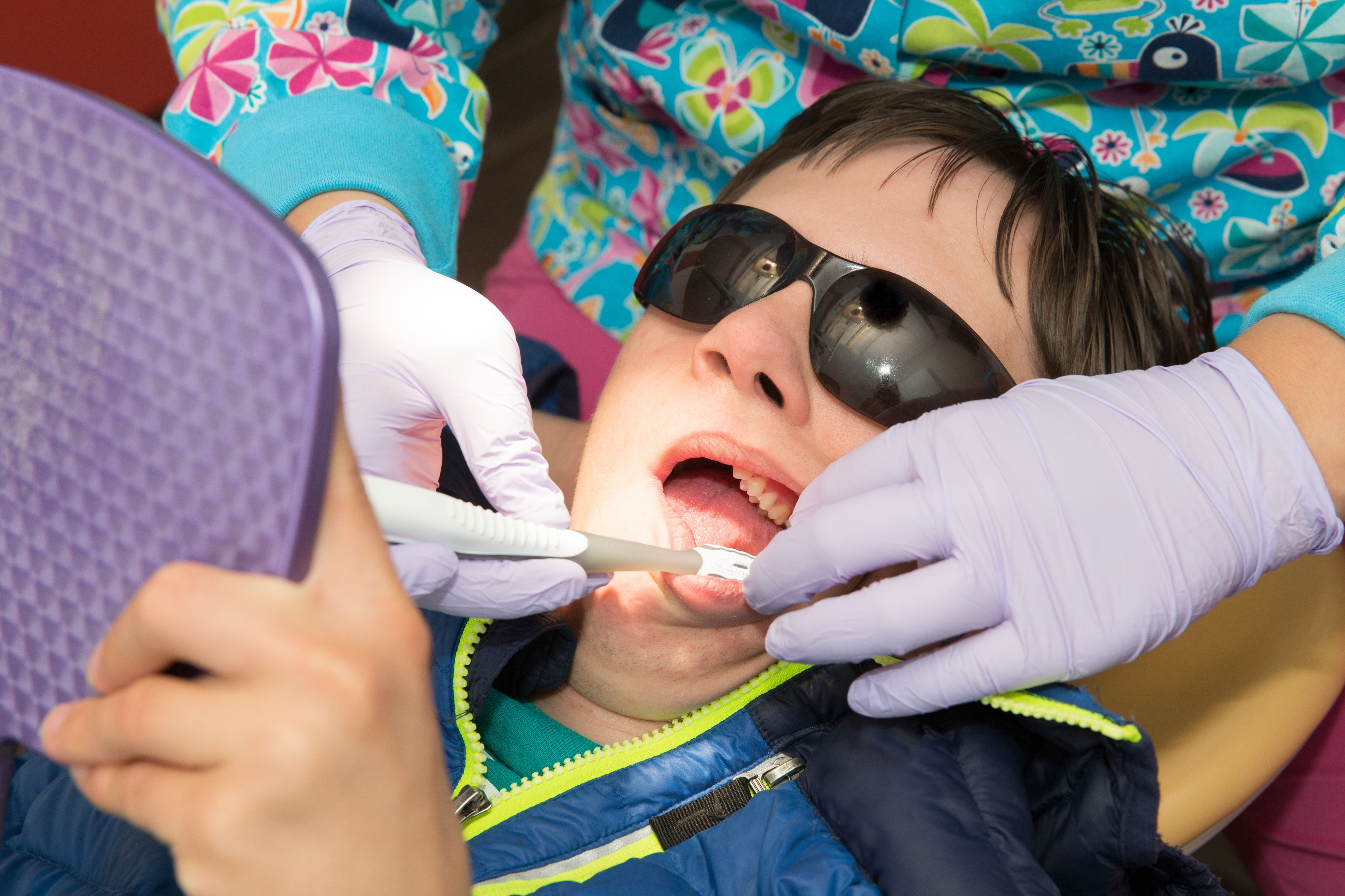 photo of a young man having teeth cleaned at a dental office