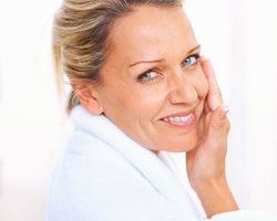 Smiling woman in bath robe holding hand to cheek