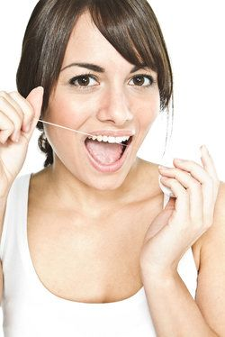 Excited brunette getting ready to floss her teeth