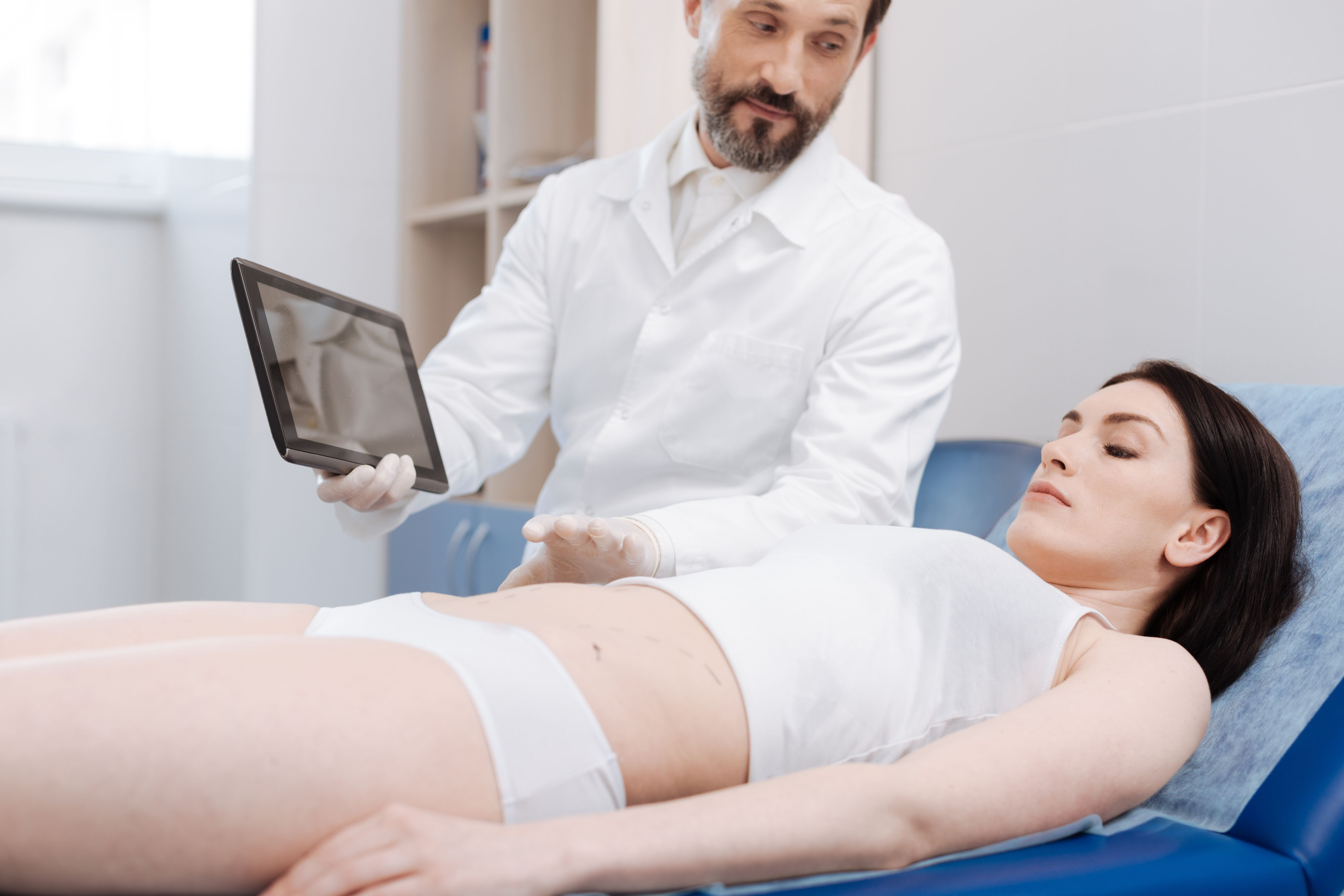 woman laying on exam bed looking at ipad with doctor