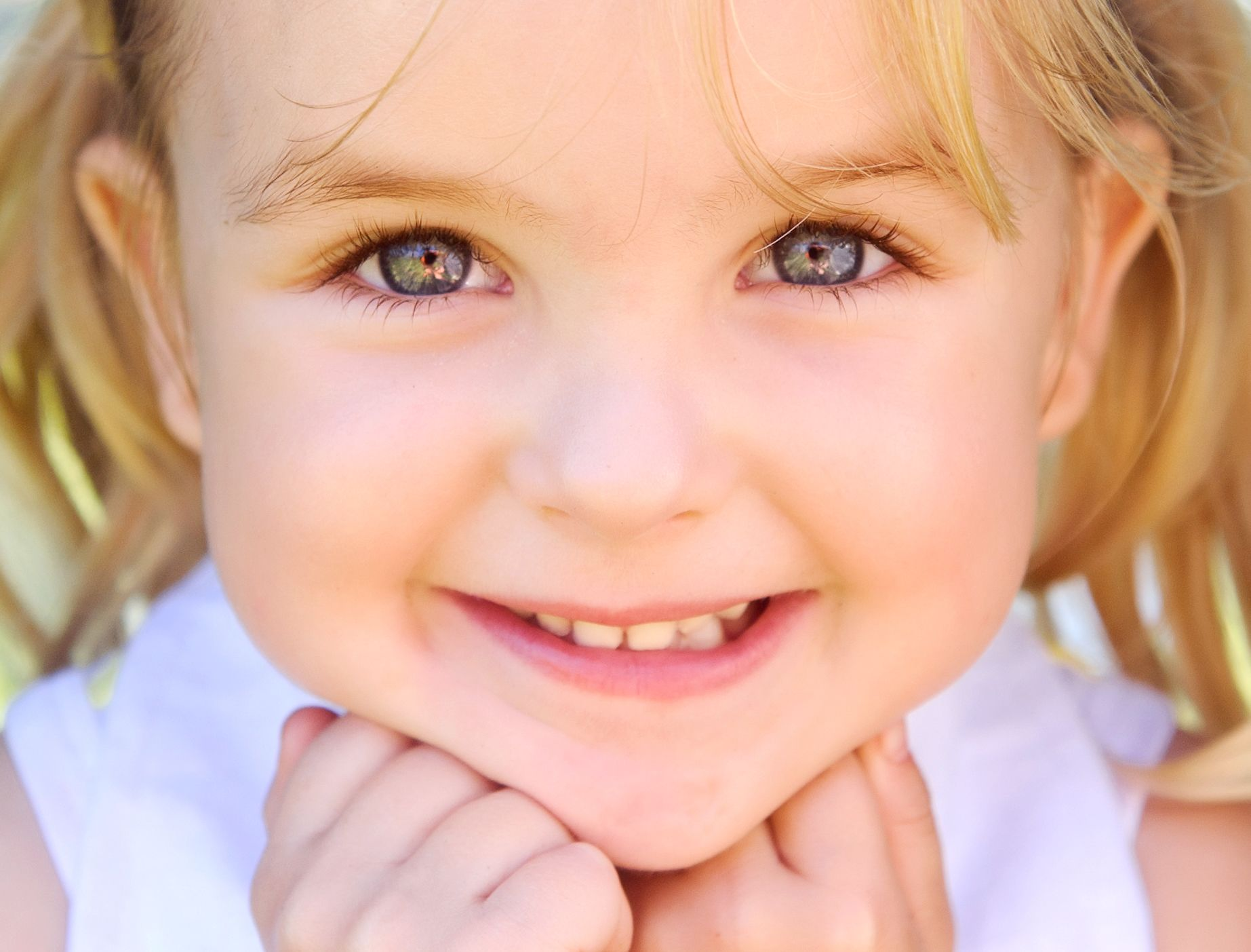 portrait of a little girl with her hands on chin smiling at camera