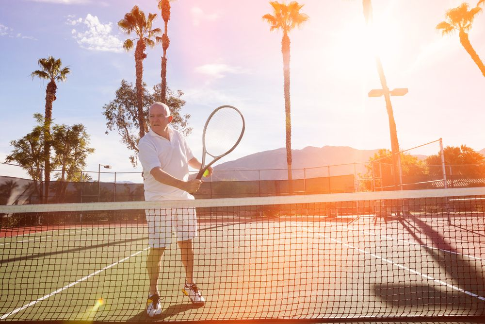 Man playing tennis in the sun