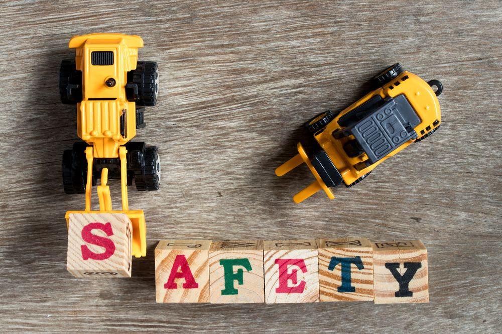 """Toy construction vehicles spelling """"safety"""" with building blocks"""