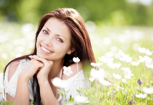 Beautiful young Caucasian woman laying in flower field, smiling with hands clasped under chin